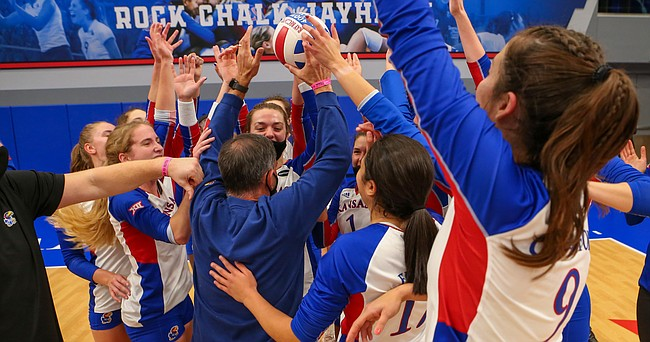 The Kansas volleyball team mobs head coach Ray Bechard after a four-set victory over Kansas State on Thursday, Oct. 29, 2020, at Horejsi Family Volleyball Arena. The victory was the 400th of Bechard's KU career.