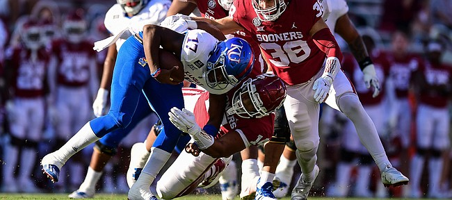 A trio of Oklahoma defenders closes in on Kansas quarterback Jalon Daniels on Nov. 7, 2020, in Norman, Okla.