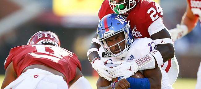 Oklahoma linebacker Brian Asamoah (24) tackles Kansas quarterback Jalon Daniels (17)  during an NCAA college football game in Norman, Okla., Saturday, Nov. 7, 2020. (Ian Maule/Tulsa World via AP)