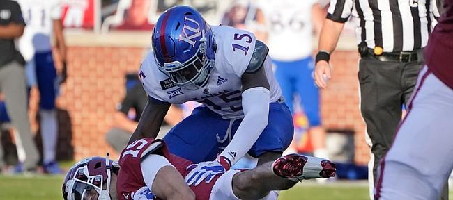 Oklahoma quarterback Tanner Mordecai (15) is sacked by Kansas linebacker Kyron Johnson (15) during an NCAA college football game in Norman, Okla., Saturday, Nov. 7, 2020. (AP Photo/Sue Ogrocki)