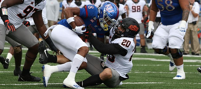 KU's Kwamie Lassiter Jr., is dragged down by an Oklahoma State defender during the Jayhawks' 47-7 loss to OSU on Saturday, Oct. 3, 2020 at David Booth Kansas Memorial Stadium.