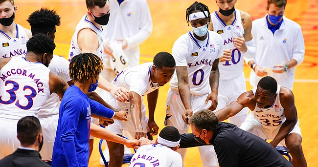 Kansas players come in for a fist bump after a timeout in the second half on Thursday, Dec. 3, 2020 at Allen Fieldhouse.
