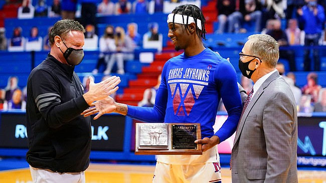 Kansas head coach Bill Self slaps hands with Kansas guard Marcus Garrett (0) after Garrett received the Naismith Defensive Player of the Year trophy prior to tipoff on Friday, Dec. 11, 2020 at Allen Fieldhouse. At right is athletic director Jeff Long.