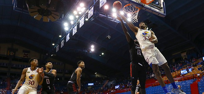 Kansas forward David McCormack (33) gets inside for a shot off the backboard past Omaha forward Wanjang Tut (13) during the second half on Friday, Dec. 11, 2020 at Allen Fieldhouse.
