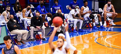 Bill Self and the Kansas bench sit socially-distanced on the sidelines as Kansas guard Tristan Enaruna (13) shoots free throws during the first half on Thursday, Dec. 3, 2020 at Allen Fieldhouse.