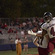 Lawrence High senior Devin Neal (4) celebrates his touchdown with teammate Ben King (17) Friday night at St. Thomas Aquinas. The Lions handed the Saints their first home loss since 2017.