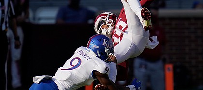 Oklahoma wide receiver Theo Wease (10) is upended by Kansas cornerback Karon Prunty (9) in the first half of an NCAA college football game in Norman, Okla., Saturday, Nov. 7, 2020. (AP Photo/Sue Ogrocki)