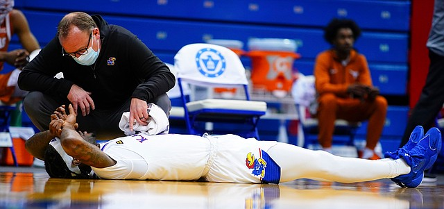Kansas guard Marcus Garrett (0) lies on his back after suffering an elbow to the head during the second half, Saturday, Jan. 2, 2021 at Allen Fieldhouse.
