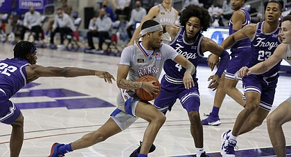 Kansas guard Dajuan Harris, center, drives to the basket as TCU guard RJ Nembhard (22), guard PJ Fuller (4) and forward Jaedon LeDee (23) defend in the first half of an NCAA college basketball game in Fort Worth, Texas, Tuesday, Jan. 5, 2021. (AP Photo/Ron Jenkins)