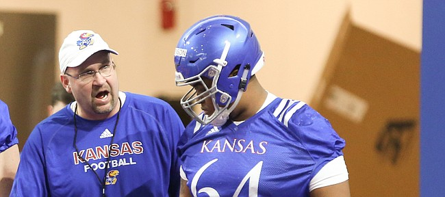 Kansas offensive line coach Luke Meadows gives instruction to lineman Jalan Robinson (54) during football practice on Wednesday, March 6, 2019 within the new indoor practice facility.