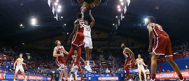 Kansas forward David McCormack (33) turns for a shot over Oklahoma forward Kur Kuath (52) with fourteen seconds to play in regulation, Saturday, Jan. 9, 2021 at Allen Fieldhouse.