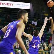 Baylor guard Jared Butler, center, scores over Kansas forward Mitch Lightfoot, left, and guard Marcus Garrett, right, in the second half of an NCAA college basketball game, Monday, Jan. 18, 2021, in Waco, Texas. (Rod Aydelotte/Waco Tribune Herald via AP)