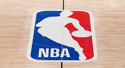 In this Aug. 28, 2020, file photo, the NBA logo in an empty basketball arena in Lake Buena Vista, Fla. (AP Photo/Ashley Landis, Pool, File)