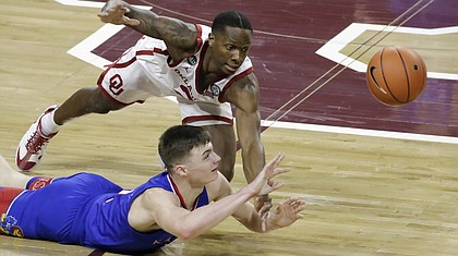 Kansas guard Christian Braun (2) and Oklahoma guard Umoja Gibson (2) fight for the ball during the first half of an NCAA college basketball game in Norman, Okla., Saturday, Jan. 23, 2021. (AP Photo/Garett Fisbeck)