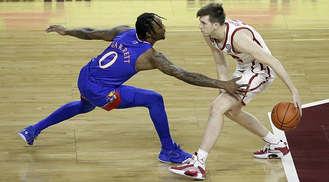Oklahoma guard Austin Reaves (12) goes against Kansas guard Marcus Garrett (0) during the first half of an NCAA college basketball game in Norman, Okla., Saturday, Jan. 23, 2021. (AP Photo/Garett Fisbeck)