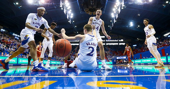 Kansas forward Mitch Lightfoot (44) and Kansas guard Dajuan Harris (3) help Kansas guard Christian Braun (2) off the floor after Braun took a charge during the first half, Saturday, Jan. 9, 2021 at Allen Fieldhouse.