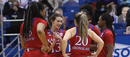 Members of the Kansas women's basketball team, including Holly Kersgieter (No. 13) and Julie Brosseau (No. 20) huddle up during the Jayhawks' home win over rival Kansas State on Jan. 23, 2021, at Allen Fieldhouse.