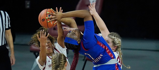 Kansas forward Tina Stephens (1) is defended by Oklahoma guard Gabby Gregory (12), guard Navaeh Tot, left, and guard Tatum Veitenheimer, right, in the first half of an NCAA college basketball game Wednesday, Jan. 27, 2021, in Norman, Okla. (AP Photo/Sue Ogrocki)