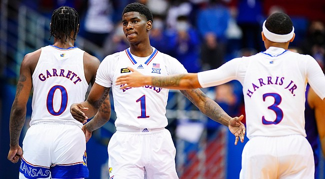 Kansas guard Tyon Grant-Foster (1) slaps hands with Kansas guard Dajuan Harris (3) and Kansas guard Marcus Garrett (0) after a bucket during the second half on Thursday, Jan. 28, 2021 at Allen Fieldhouse.