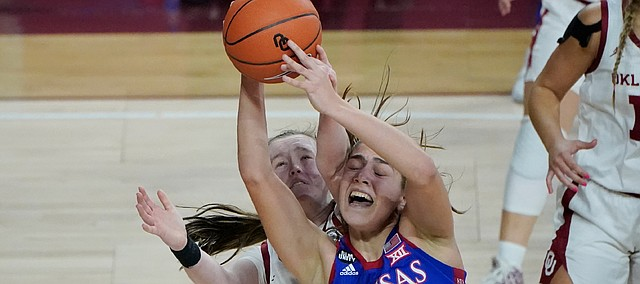 Kansas forward Ioanna Chatzileonti (11) is fouled by Oklahoma guard Taylor Robertson, left, in the second half of an NCAA college basketball game Wednesday, Jan. 27, 2021, in Norman, Okla. (AP Photo/Sue Ogrocki)