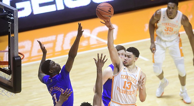 Tennessee forward Olivier Nkamhoua (13) shoots the ball over Kansas guard Tyon Grant-Foster (1) during a basketball game between the Tennessee Volunteers and the Kansas Jayhawks at Thompson-Boling Arena in Knoxville, Tennessee on Saturday, January 30, 2021.