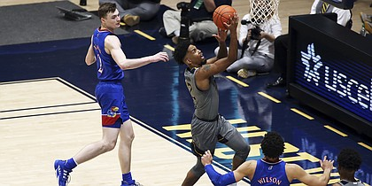West Virginia guard Taz Sherman (12) shoots while defended by Kansas guard Christian Braun (2) during the second half of an NCAA college basketball game Saturday, Feb. 6, 2021, in Morgantown, W.Va. (AP Photo/Kathleen Batten)