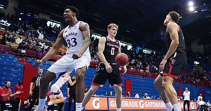 Kansas forward David McCormack (33) reacts after scoring against Texas Tech guard Mac McClung (0) and guard Kevin McCullar (15) during the first half at Allen Fieldhouse Saturday afternoon in Allen Fieldhouse on Feb. 20, 2021. Photo by Jay Biggerstaff-USA TODAY Sports.