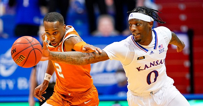 Kansas guard Marcus Garrett (0) and Texas guard Matt Coleman III (2) compete for a loose ball during the second half, Saturday, Jan. 2, 2021 at Allen Fieldhouse.