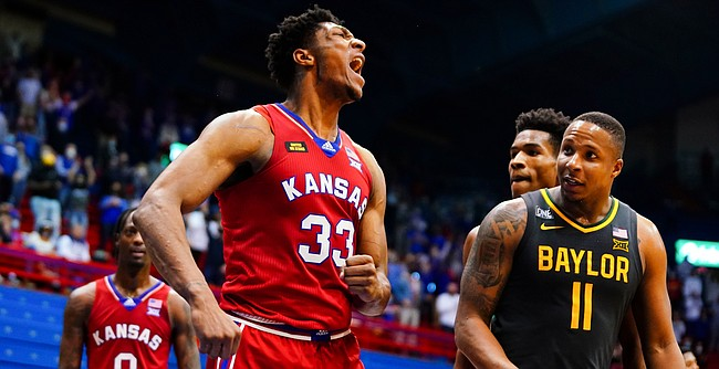 Kansas forward David McCormack (33) roars after swatting a Baylor shot late in the second half on Saturday, Feb. 27, 2021 at Allen Fieldhouse. At right is Baylor guard Mark Vital (11).