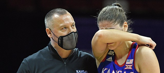 Kansas women's basketball coach Brandon Schneider consoles forward Ioanna Chatzileonti during the Jayhawks' loss to TCU during the Phillips 66 Big 12 Women's Basketball Championship at Municipal Auditorium in Kansas City, Missouri on March 11, 2021.