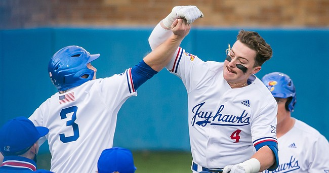 Kansas freshman Anthony Tulimero (4) celebrates his seventh-inning home run with sophomore Casey Burnham during a 10-9, comeback victory by the Jayhawks over Missouri on Tuesday, March 30, 2021, at Hoglund Ballpark.