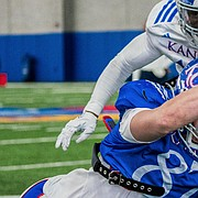 Kansas tight end Will Huggins dives forward with the ball in his hands during the Jayhawks' scrimmage on Saturday, April 17, 2021, at KU's indoor practice facility.