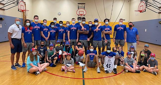 Several members of the 2021-22 Kansas men's basketball team pose for a photo with 14 Boys & Girls Club members at Prairie Park Elementary School after staging a surprise scrimmage on Monday, July 19, 2021.