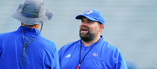 Kansas offensive coordinator Andy Kotelnicki talks with another member of the coaching staff during practice on Saturday, Aug. 14, 2021 at Memorial Stadium.