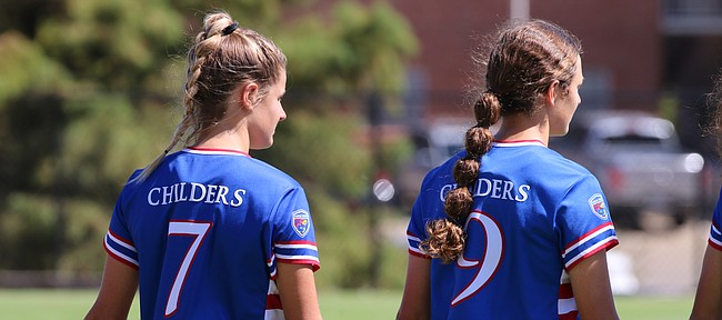 Sisters and Kansas soccer teammates Raena (No. 7) and Rylan Childers (No. 9) hold hands on the sideline before a game.