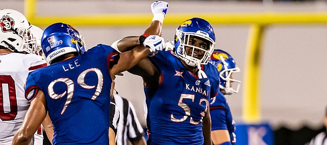 Kansas defensive lineman Caleb Taylor (No. 53) celebrates with defensive end Malcolm Lee (No. 99) after making a play in the Jayhawks' Week 1 win over South Dakota, on Sept. 3, 2021.