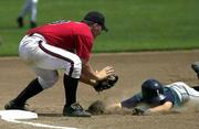 Shaun Flynn of Lawrence Raiders, dives into the out at the third base as John Norris of Wichita Bandits makes the tag during the Al Ice Championship game held at Hoglund Ballpark.