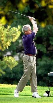 President Clinton tees off Friday at the Army Navy Golf Course in Arlington, Va.