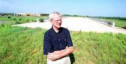 Mike Rees, chief counsel for the Kansas Department of Transportation, stands at the uncompleted South Lawrence Trafficway near 38th and Iowa Streets. Rees is working privately to get affected groups to back a plan for completion of the road.