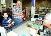 Zach Baird, 10, left, is all smiles after being the first to check out a reserved copy of the new Harry Potter and the Goblet of Fire book Saturday morning at the Lawrence Public Library. Michael Ludwick, 11, right, with his father, David, got the second book.