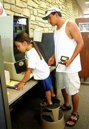 Mia Monteau, 4, uses a self-checkout machine with her father Maurice, Lawrence, Friday in the childrens area of the Lawrence library. A new automatic reader for the adult section of the library should arrive in September soon after a renovation to replace the laminate counters now in the circulation department.