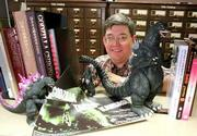 "Bill Tsutsui, an associate professor of history at Kansas University, is one of the organizers of the ""Godzilla Takes Kansas!"" festival. Tsustui is shown with some of the godzilla items he has in his collection."