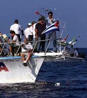 Ramon Sanchez, standing on bow of boat, along with other Cuban exiles throw flowers into the sea Saturday off the coast of Cuba. The exiles held a memorial service honoring the 41 Cubans who lost their lives on July 13, 1994, as they tried to flee Cuba.