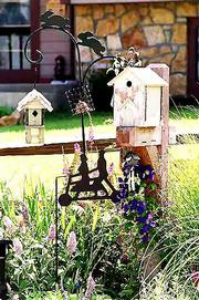 A birdhouse is surrounded by clematis at the entrance of the front yard.