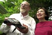 A proposed federal bill could assist research efforts of Joe Collins, Kansas University herpetologist emeritus, and his wife, Suzanne Collins, professional wildlife photographer. The couple are shown with a map turtle found in the Kansas River.