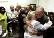 Plaintiff Ralph Della Vecchia, right, whose wife, Angie, died of cancer, hugs Margaret Amodeo, wife of plaintiff Frank Amodeo, after the jury returned a verdict Friday in the punitive phase of the Florida smokers trial. The jury ordered the tobacco industry Friday to pay $145 billion in punitive damages to sick Florida smokers.