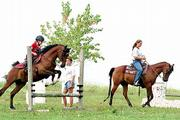 Paige Wagner, left, works a jump with her horse, Dancer, while Erica Goddard, center, watches. At right, Heather Hobbs runs her horse, Doc, through a routine at Lazy J Training Center. Wagner and Goddard will attend the International Arabian Youth Nationals next week in Oklahoma City.
