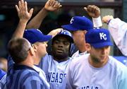 Kansas Citys Carlos Febles, center, is congratulated by teammates after scoring on a bases-loaded walk. The Royals beat the Indians Thursday at Cleveland.