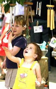 Wind chimes at Natural Way, 820 Mass., caught the attention of Hannah Gerace, 3, and her big sister Allie, 6, of Lawrence.