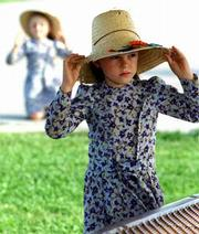 Margaret Dyck, 7, adjusts her straw hat Thursday as the wind tries to blow it off in Holcomb. Her sister, Mary, 6, also struggles to keep her hat on in the background. Windy weather Thursday plagued southeast Kansas.